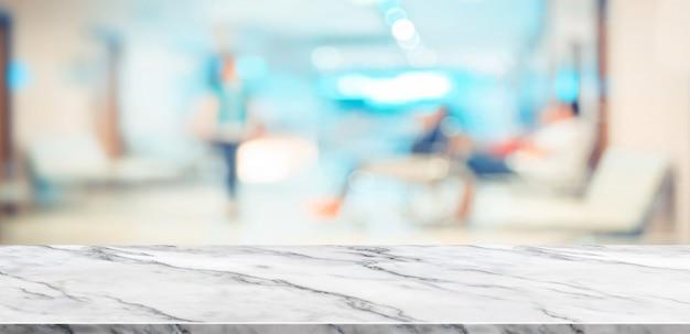 Vista superior de la mesa de mármol blanco vacío con paciente borrosa en el fondo del hospital Foto Premium