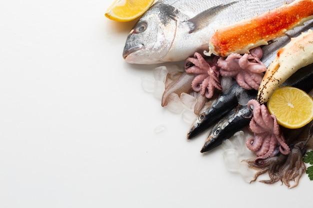 Vista superior mezcla de mariscos con limones Foto gratis