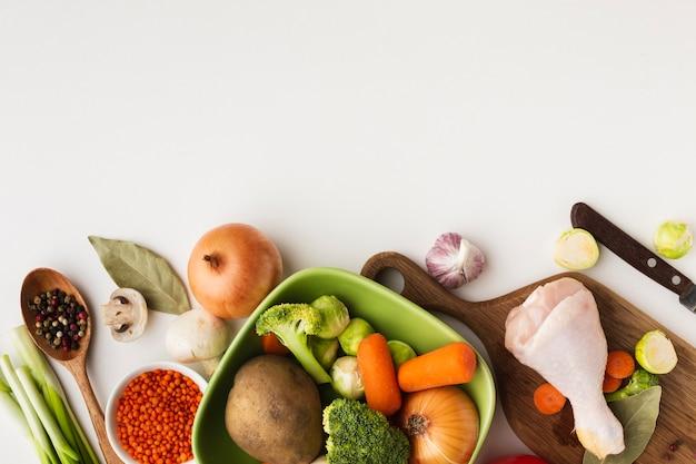 Vista superior mezcla de verduras en la tabla de cortar y en un recipiente con espacio de copia Foto gratis