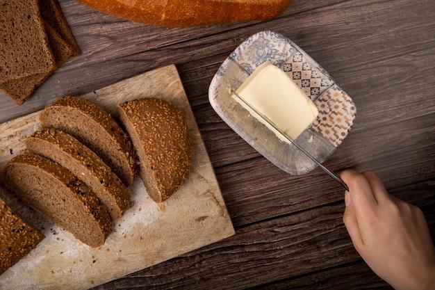 Vista superior de la mujer mano cortando mantequilla con cuchillo y pan de molde en rodajas en la tabla de cortar sobre fondo de madera Foto gratis
