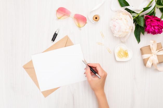Vista superior mujer mano escribiendo la tarjeta de invitación de boda o carta de amor. Foto Premium