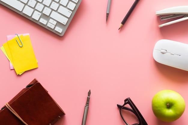 Vista superior de la oficina de escritorio rosa pastel con espacio de copia para ingresar el texto. Foto Premium
