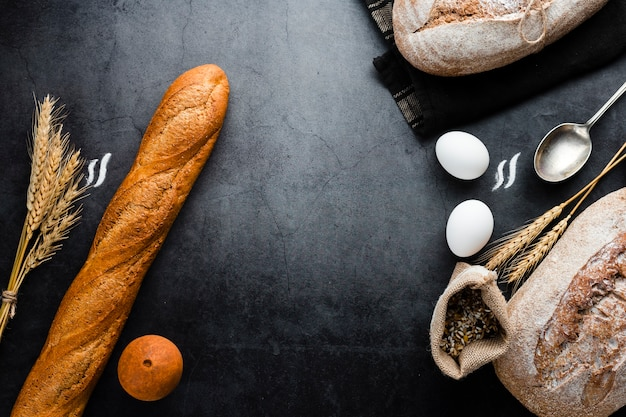 Vista superior de pan e ingredientes sobre fondo negro Foto gratis