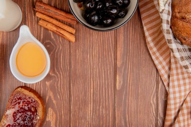 Vista superior de panes como pan negro rebanada de pan de centeno con mermelada mantequilla canela aceitunas en tazón de leche sobre fondo de madera con espacio de copia Foto gratis