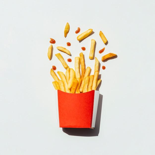 Vista superior papas fritas en una caja roja Foto gratis
