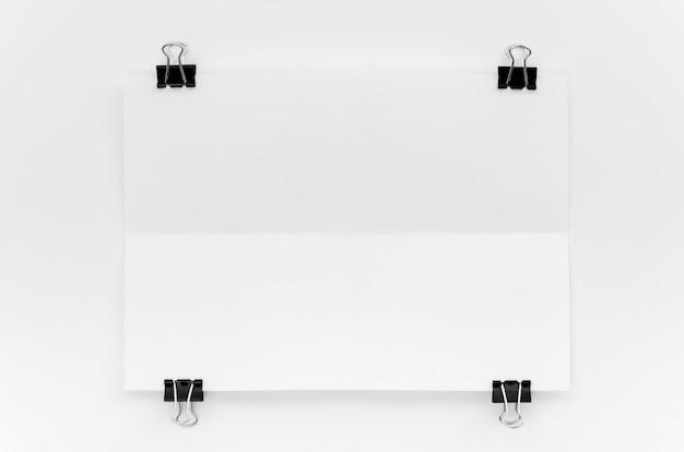 Vista superior de papel con clips metálicos en las esquinas Foto gratis