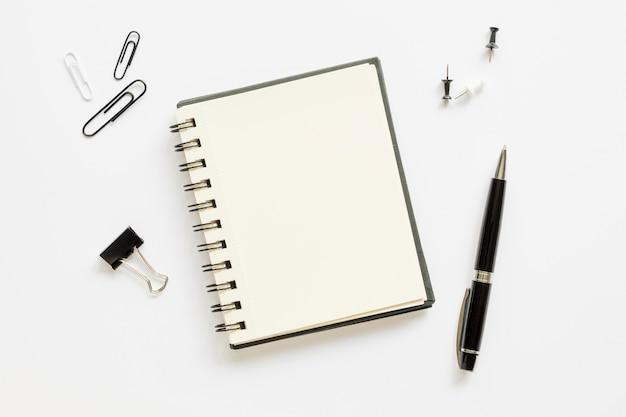 Vista superior de papelería de oficina con libreta y alfileres de papel Foto gratis