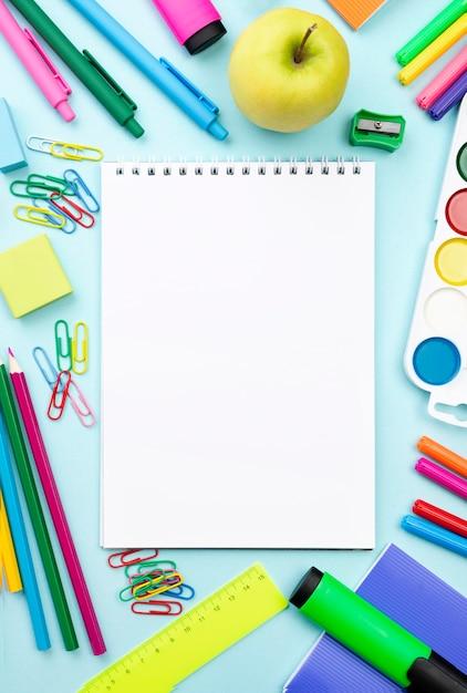 Vista superior de papelería de regreso a la escuela con cuaderno y manzana Foto Premium