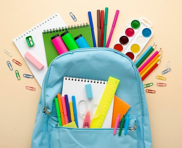 Vista superior de papelería de regreso a la escuela con mochila y lápices de colores. Foto Premium