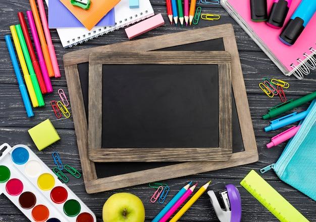 Vista superior de papelería de regreso a la escuela con pizarras Foto gratis