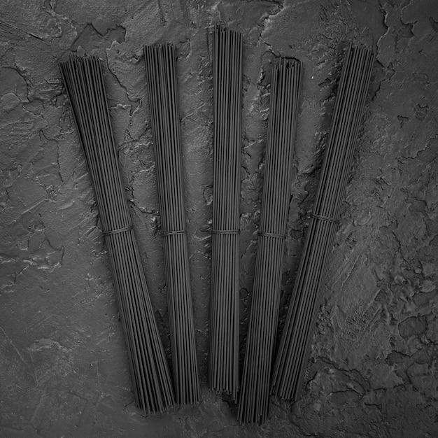 Vista superior de paquetes de espagueti negro en pizarra Foto gratis