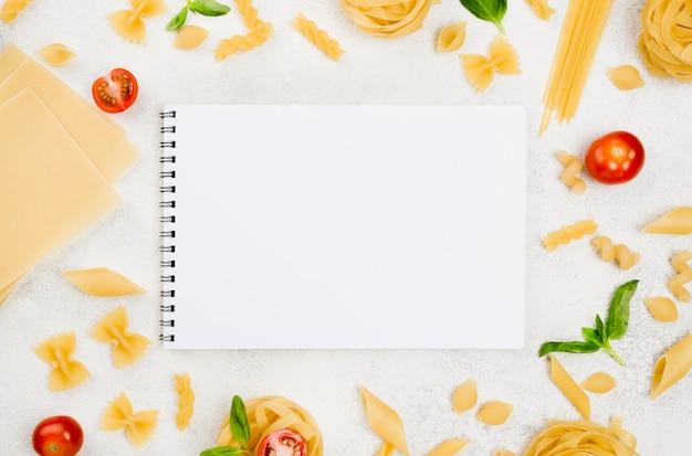 Vista superior de pasta italiana y cuaderno Foto gratis