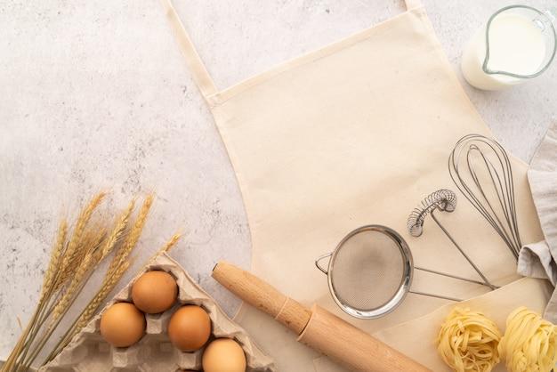 Vista superior de pasta con marco de ingredientes con delantal Foto Premium