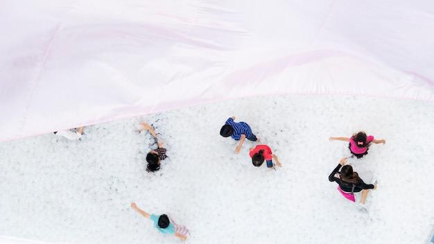 Vista superior del patio de recreo con globos con gente de la familia y niños jugando a la pelota blanca con el techo de tela textil en primer plano Foto Premium