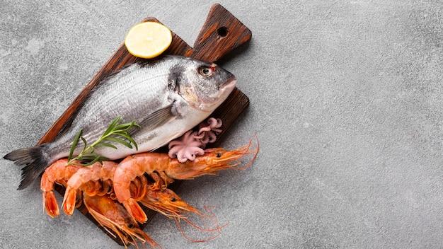 Vista superior de peces y camarones sobre fondo de madera Foto Premium