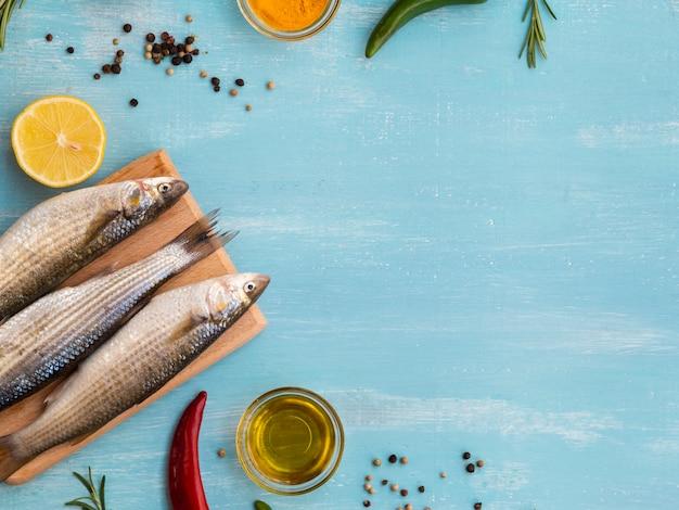 Vista superior de peces crudos en una tabla de madera Foto gratis