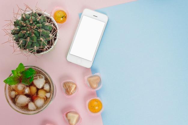 Vista superior pequeño cactus verde, cóctel frío, teléfono y dulces sobre fondo rosa y azul con espacio de copia. Foto Premium