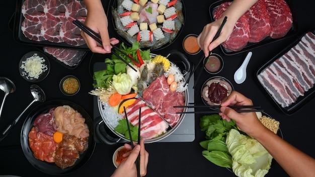 Vista superior de las personas que comen shabu-shabu en una olla caliente con carne fresca en rodajas, mariscos y verduras con fondo negro Foto Premium