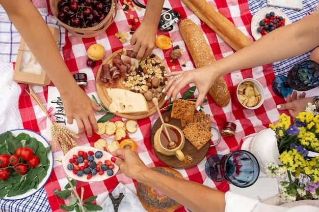 Vista superior personas toman comida de manta de picnic a cuadros. Foto Premium