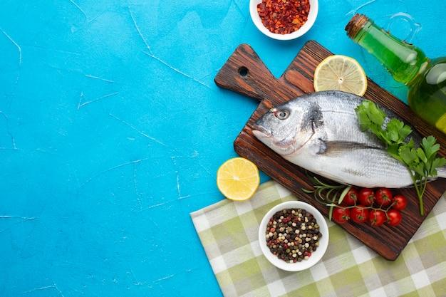 Vista superior de pescado fresco con condimentos en la mesa Foto gratis