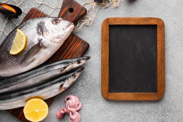 Vista superior de pescado fresco en el fondo de madera Foto gratis