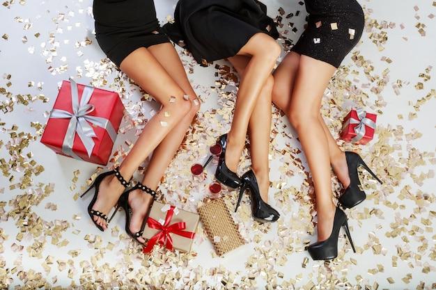 Vista superior de las piernas de mujeres sexy sobre fondo de confeti dorado brillante, cajas de regalo, copas de champán Foto gratis