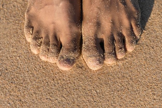 Vista superior de los pies descalzos sobre la arena Foto gratis