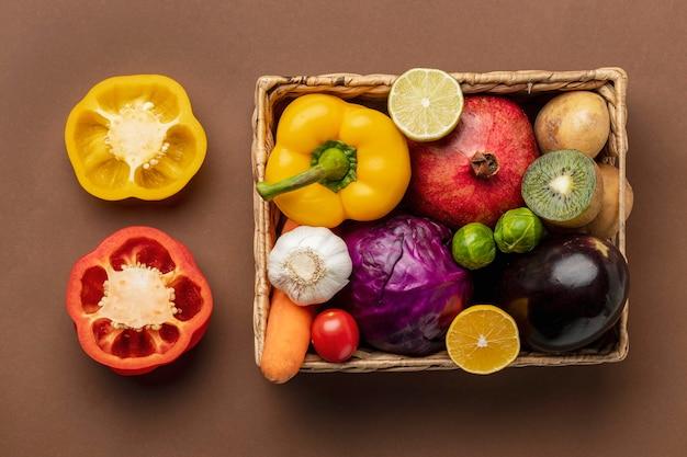 Vista superior de pimientos con canasta de verduras Foto gratis