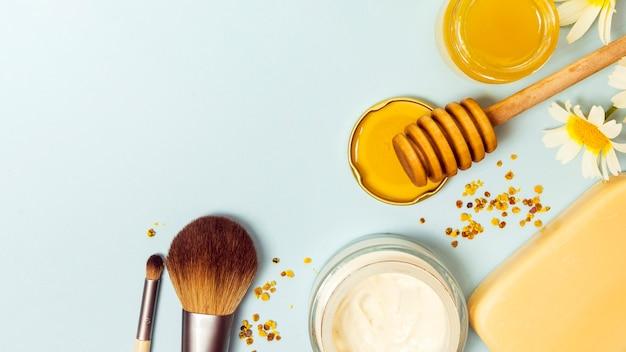 Vista superior del pincel de maquillaje; crema; miel; jabón; polen de abeja y flor blanca Foto gratis