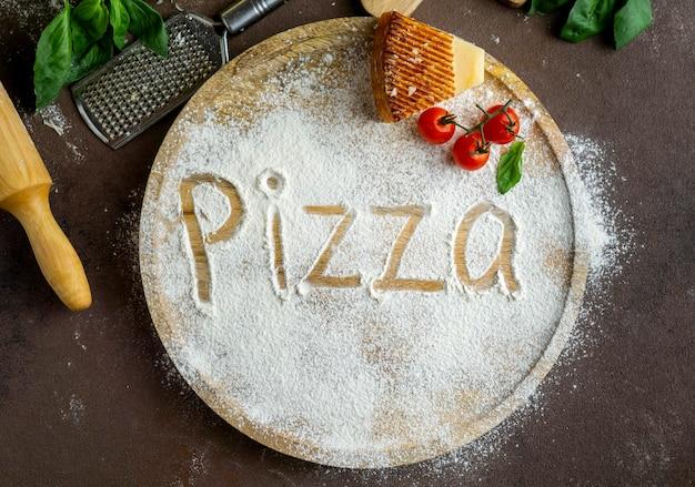 Vista superior de la pizza escrita en harina con queso parmesano y tomates Foto gratis
