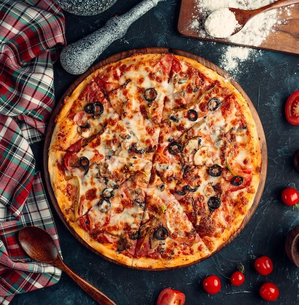 Vista superior de pizza mixta con tomate, aceituna negra y queso fundido Foto gratis