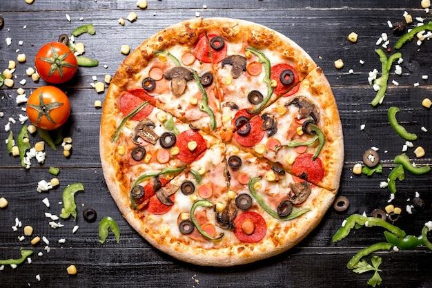 Vista superior de pizza de pepperoni con salchichas de champiñones pimiento verde oliva y maíz en madera negra Foto gratis