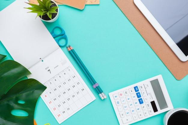 Vista superior plano del espacio de trabajo escritorio estilo diseño suministros de oficina con calendario Foto Premium