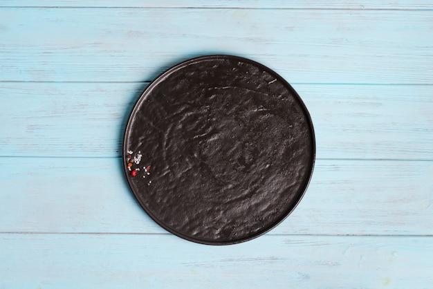 Vista superior del plato de cerámica oscura con especias y sal Foto Premium