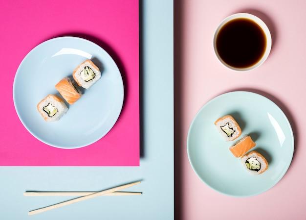 Vista superior de platos de sushi con palillos y salsa de soja Foto gratis