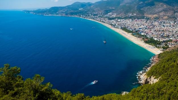 Vista superior de la playa de alanya en la montaña con el ferry de la costa en el mar azul y el fondo de la ciudad del puerto - hermosa playa de cleopatra alanya turquía paisaje histórico de viaje Foto Premium