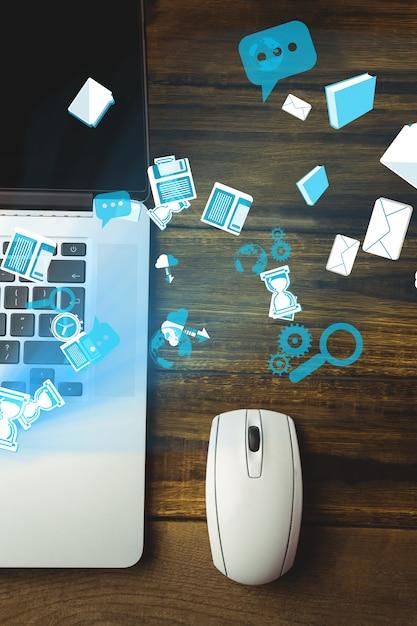Vista superior de portatil y ratón con iconos tecnológicos Foto gratis