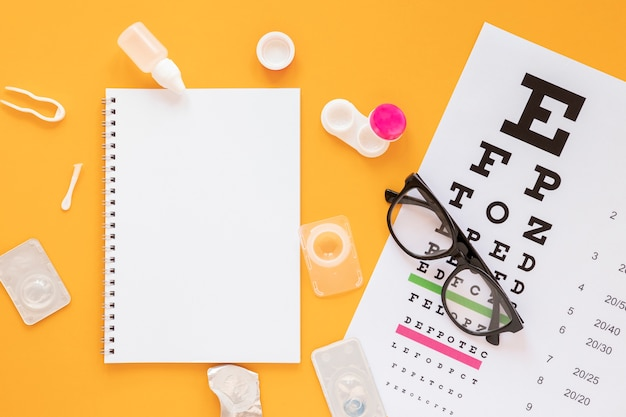 Vista superior de productos de consulta óptica con maqueta de cuaderno Foto gratis