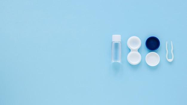 Vista superior de productos para el cuidado de los ojos sobre fondo azul con espacio de copia Foto gratis