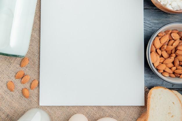 Vista superior de productos lácteos como almendras de requesón de leche alrededor del bloc de notas sobre tela de saco y fondo de madera con espacio de copia Foto gratis
