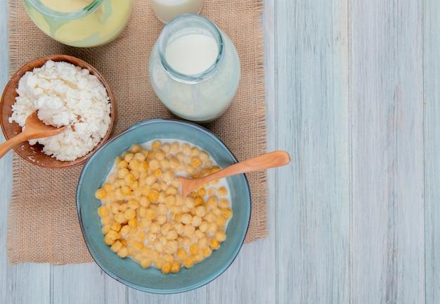 Vista superior de productos lácteos como leche condensada de requesón sobre tela de saco y fondo de madera con espacio de copia Foto gratis