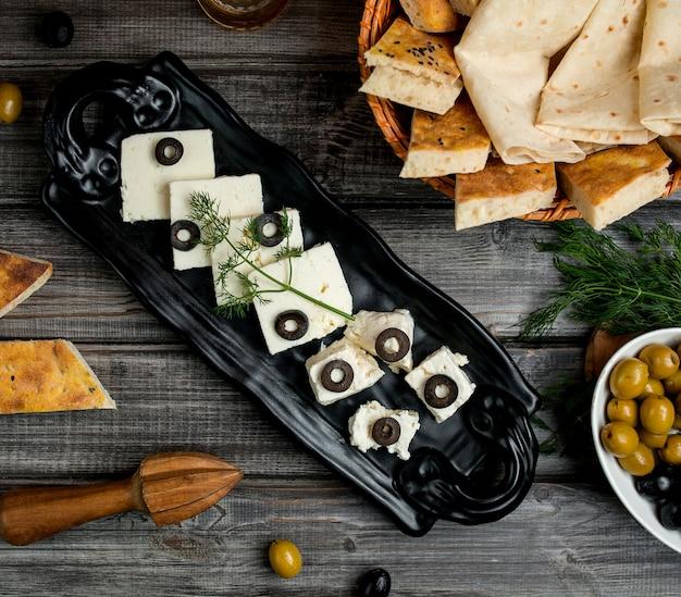 Vista superior de queso blanco y de cabra cubierto con rodajas de aceituna Foto gratis