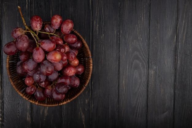 Vista superior de un racimo de uvas frescas dulces en una cesta de mimbre en la mesa de madera oscura con espacio de copia Foto gratis