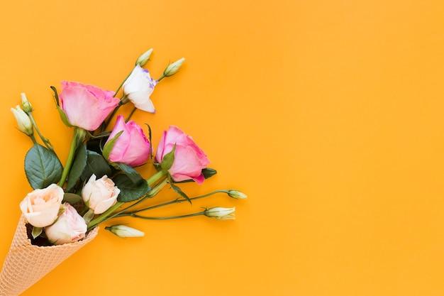 Vista superior ramo de rosas sobre fondo naranja espacio de copia Foto gratis