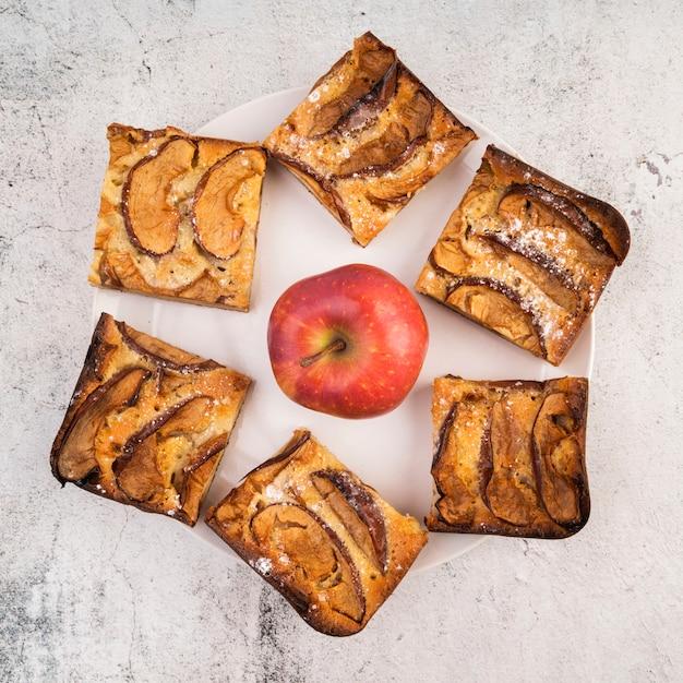 Vista superior rebanadas de pastel y una manzana sobre la mesa Foto gratis