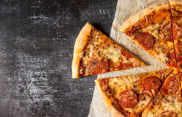 Vista superior rebanadas de pizza de salami Foto gratis