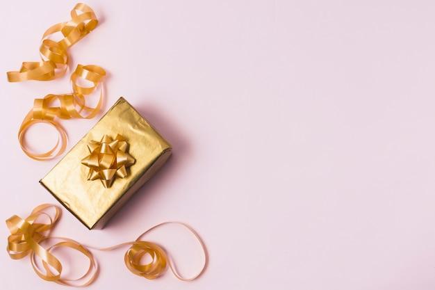 Vista superior de regalo dorado con cinta Foto gratis