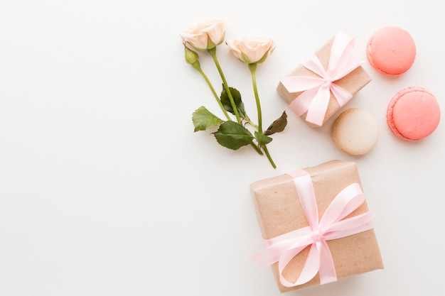 Vista superior de regalos con macarons y rosas Foto gratis