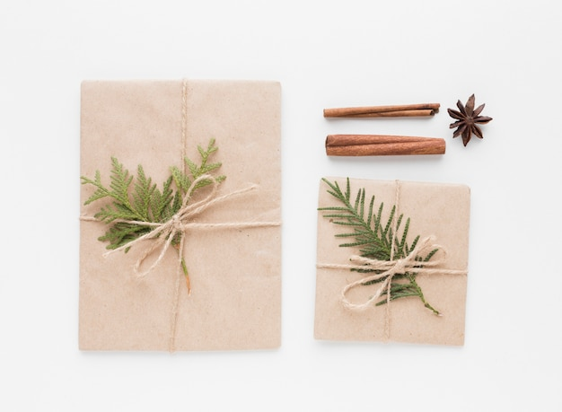 Vista superior de regalos con ramas y hojas de canela Foto gratis
