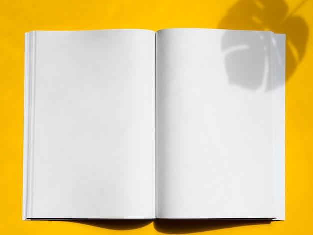 Vista superior revista maqueta con fondo amarillo Foto gratis